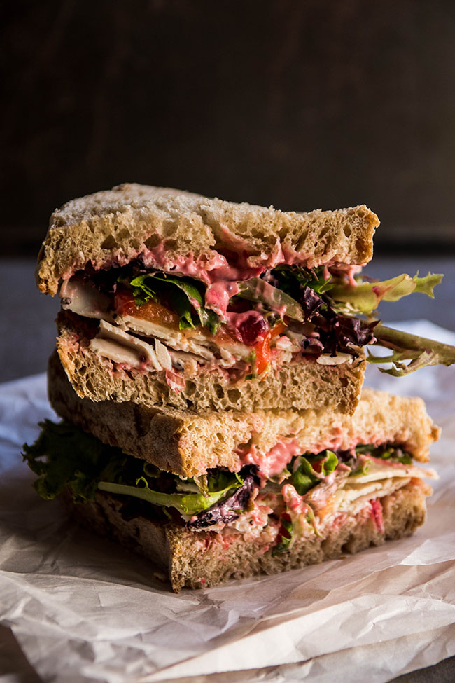 Two sandwich halves stacked on top of each other, with Thanksgiving turkey, cranberry mayonnaise, greens, and tomatoes.