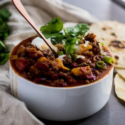 White bowl of chili topped with cilantro and sour cream.