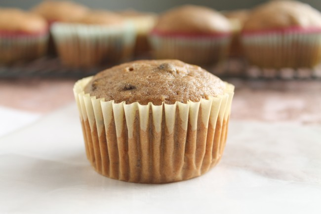 Banana chocolate chip muffin in a light yellow wrapper, sitting in front of a wire cooling rack filled with more muffins.