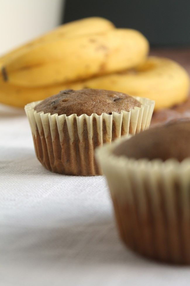 Dark brown muffin in a light yellow wrapper next to a bunch of bananas.