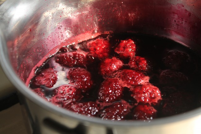 Close up of blackberry rum sauce cooking in a saucepan.