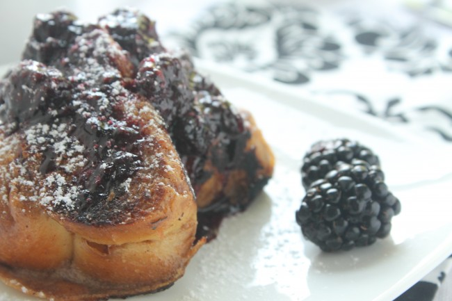 Slices of french toast on a white plate next to fresh blackberries.