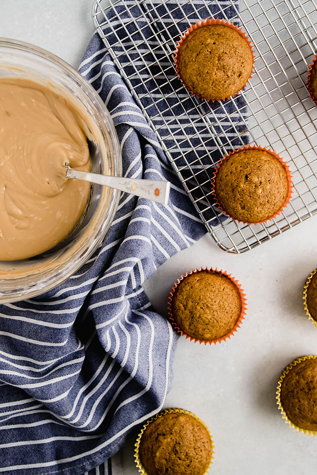 overhead photo of unfrosted pumpkin cupcakes on a cooling rack next to a blue tea towel and a bowl of maple frosting