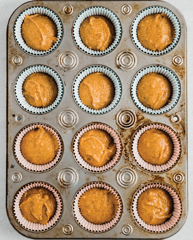 overhead photo of a cupcake tin full of orange batter waiting to be baked
