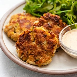 Three crab cakes on a white plate next to a small bowl of aioli