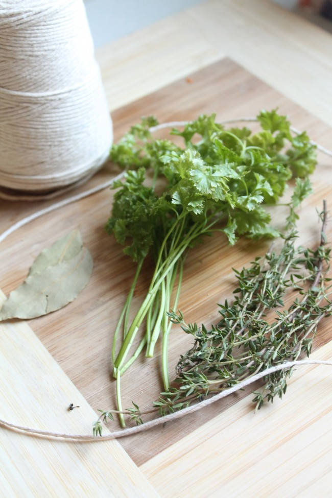 Fresh herbs on a wooden cutting board next to a roll of kitchen twine.