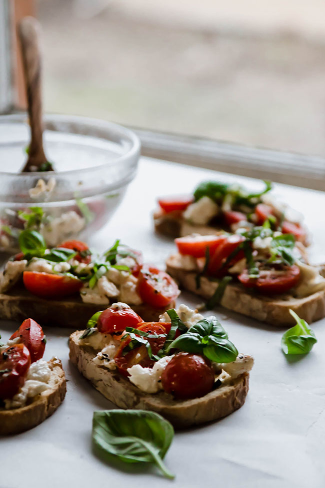 Four pieces of bruschetta toast next to a glass mixing bowl in front of a kitchen window.
