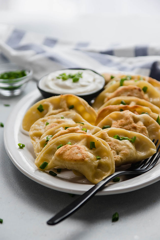 pierogi garnished with chopped chives on a white plate with a black serving fork