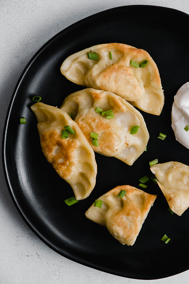pierogi topped with chives on a large black plate