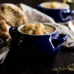 Potato soup in a dark blue bowl with a dark background and a light linen napkin