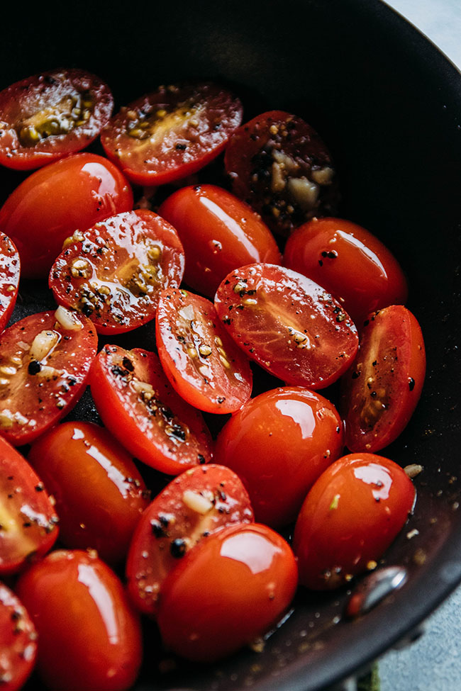 halved cherry tomatoes in a skillet with garlic