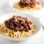 Italian sausage bolognese in a white bowl.