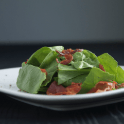 Spinach and prosciutto on a square white plate.