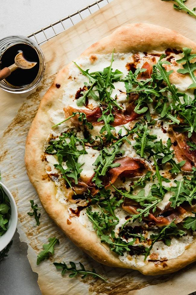 Overhead photo of white pizza topped with prosciutto and arugula next to a small glass jar of balsamic vinegar on a white background