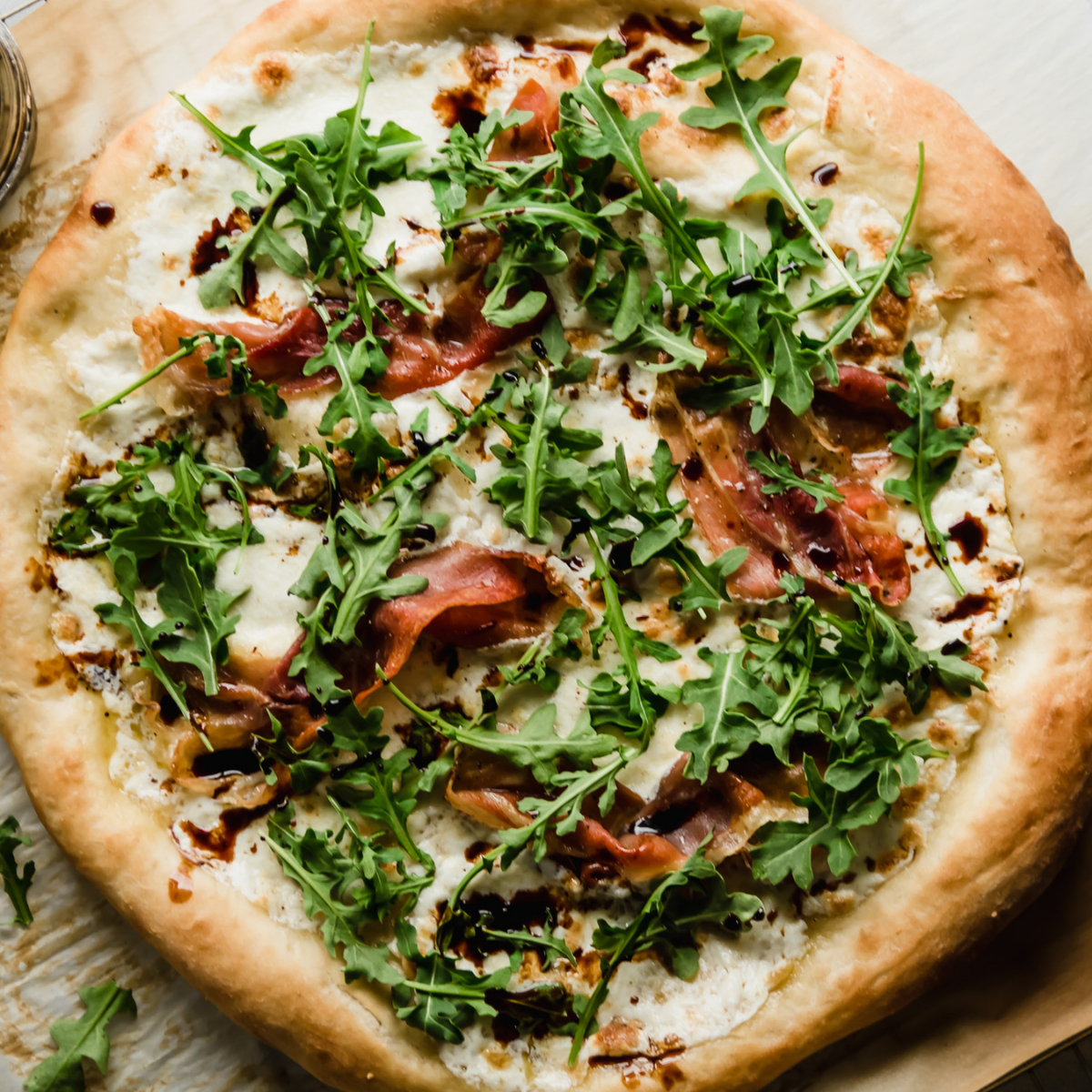 White pizza topped with prosciutto, arugula, and mozzarella, sitting on a wire cooling rack.