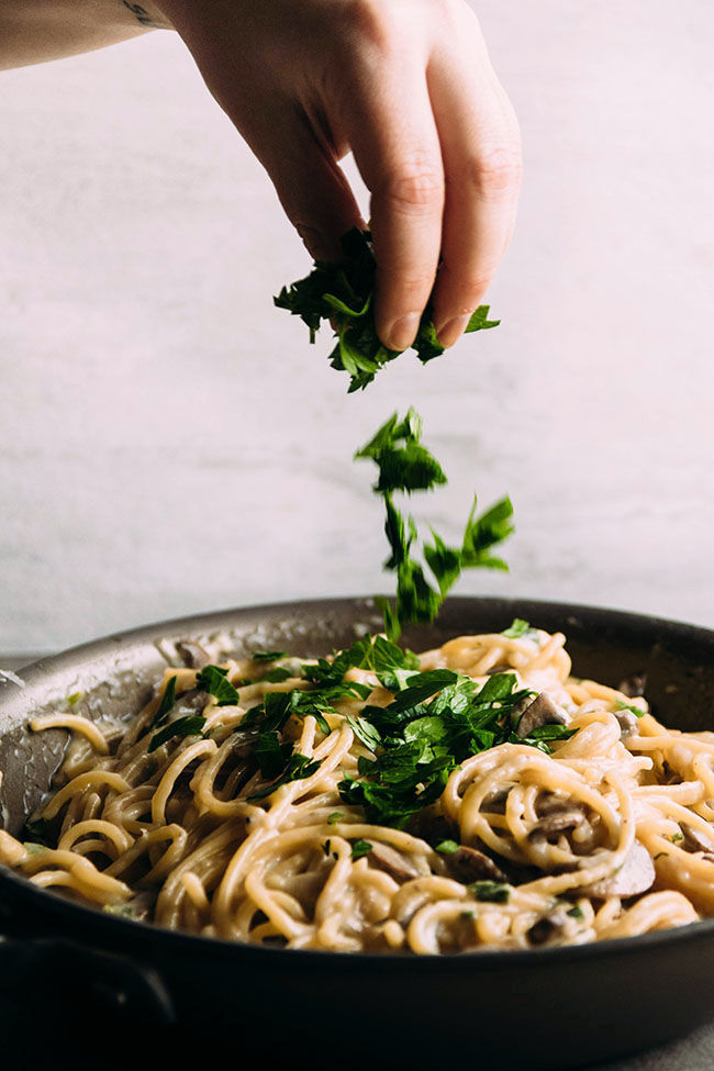 Hand sprinkling fresh parsley over spaghetti in a dark skillet.