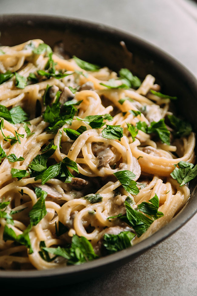 Close up side photograph of spaghetti with white sauce and mushrooms in a dark grey skillet, topped with chopped parsley