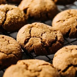 Gingersnap cookies grouped close together on a wire cooling rack.