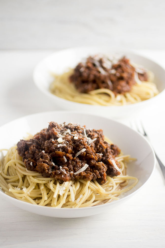 Two white bowls filled with cooked spaghetti and topped with bolognese sauce.