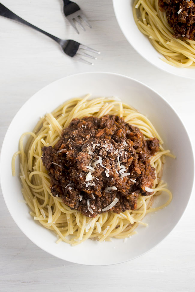 Spaghetti in a shallow white bowl, topped with dark red bolognese sauce and parmesan cheese.
