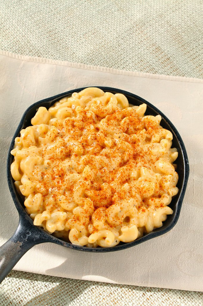 Creamy macaroni and cheese in a cast iron skillet, topped with a sprinkle of paprika.