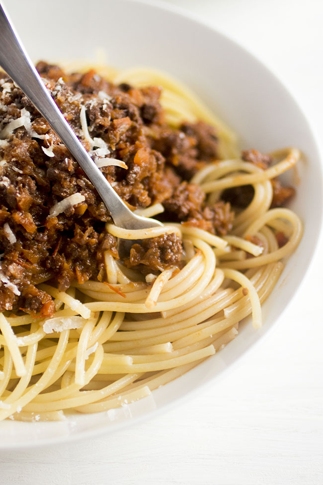 Silver fork twirling spaghetti strands with dark red bolognese sauce in a white bowl.