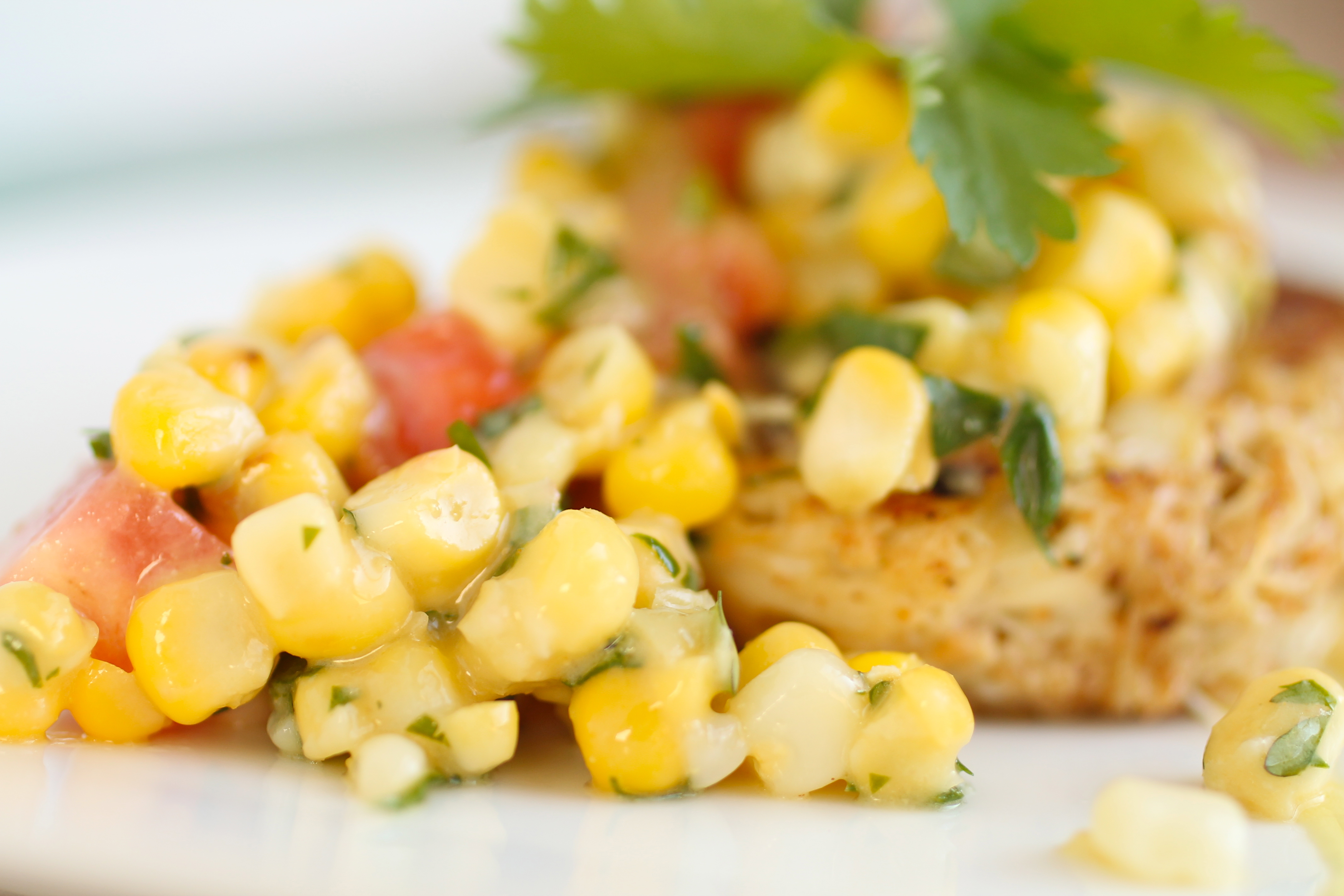 Close up of a crab cake topped with corn salsa and a sprig of fresh cilantro.