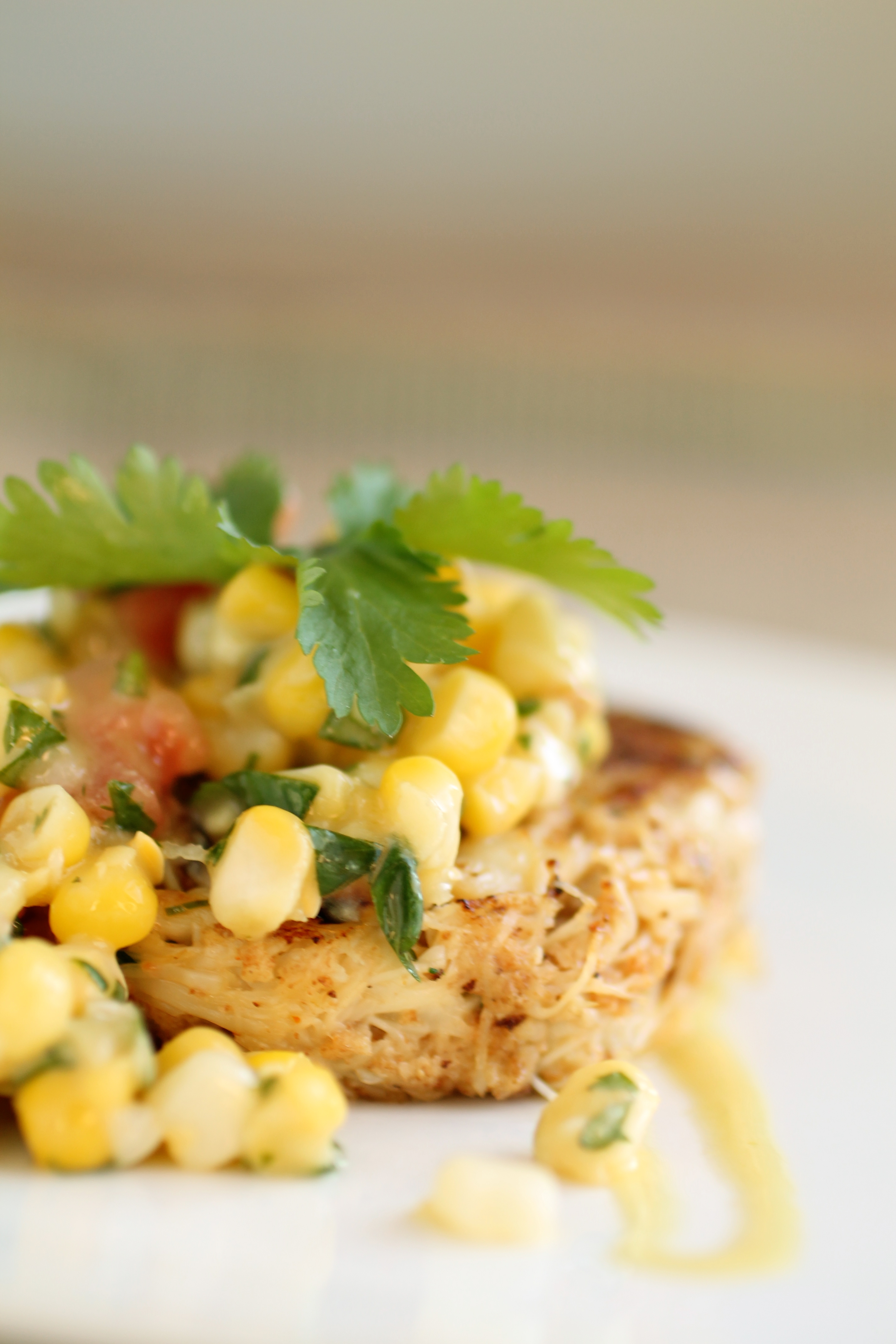 Crab cake topped with corn salsa and a sprig of fresh cilantro.