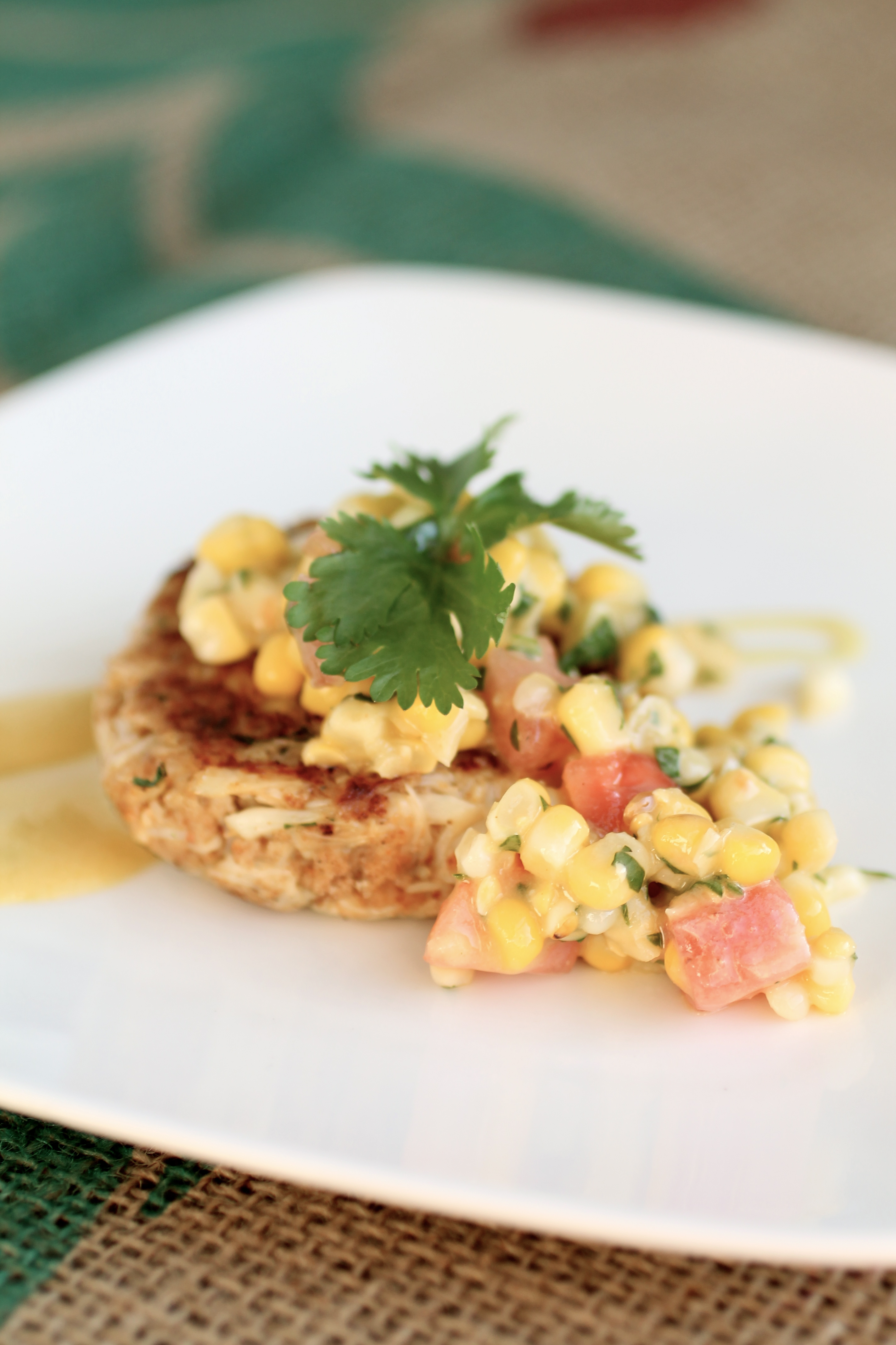Crab cake topped with corn salsa and a sprig of fresh cilantro on a square white plate.