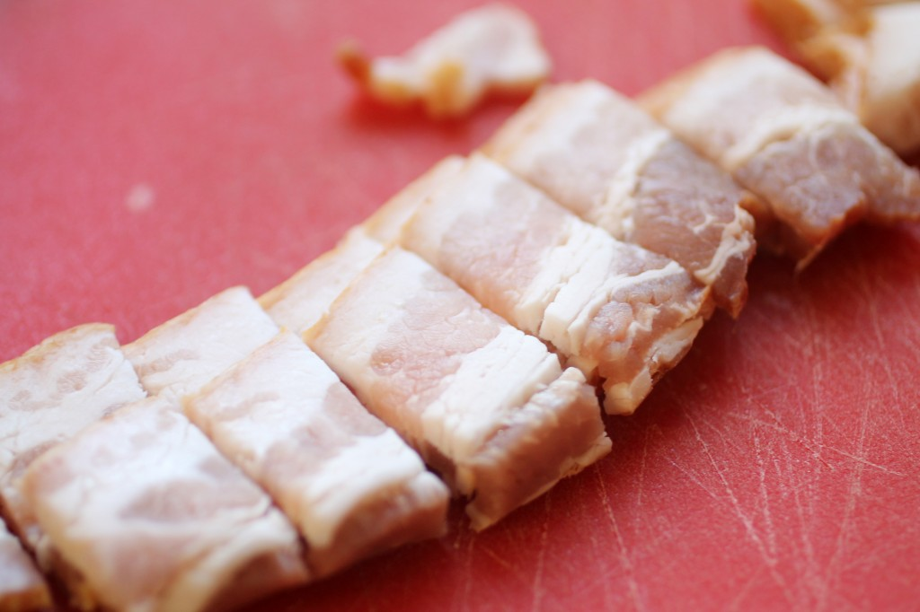 Bacon strips sliced into small pieces on a red cutting board.