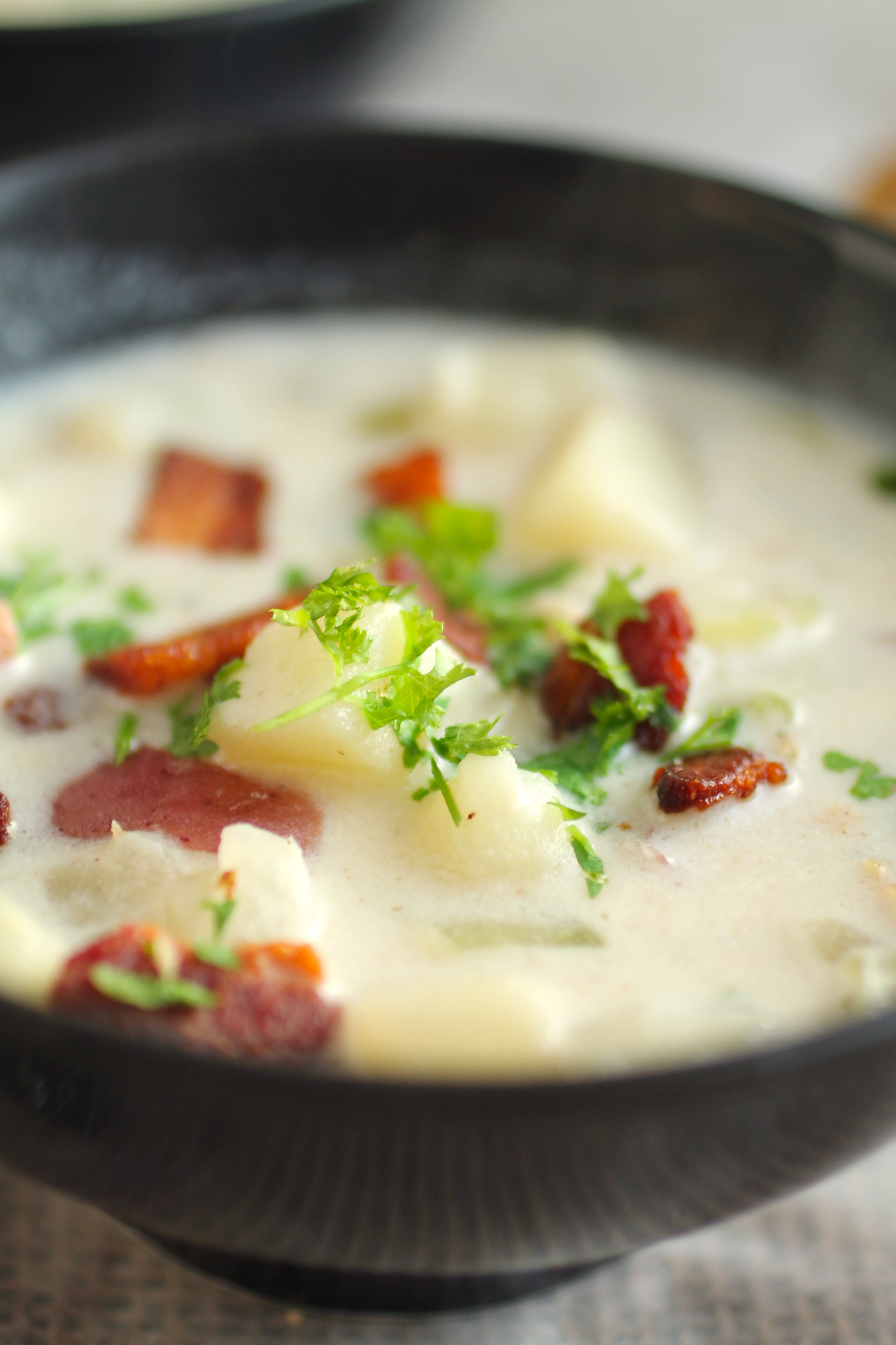 Close up of clam chowder topped with crispy bacon and chopped parsley.