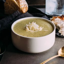 Broccoli soup topped with cheddar cheese in a white bowl.