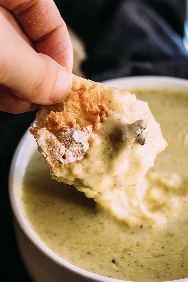 Hand dipping a piece of crusty bread into a bowl of broccoli soup.