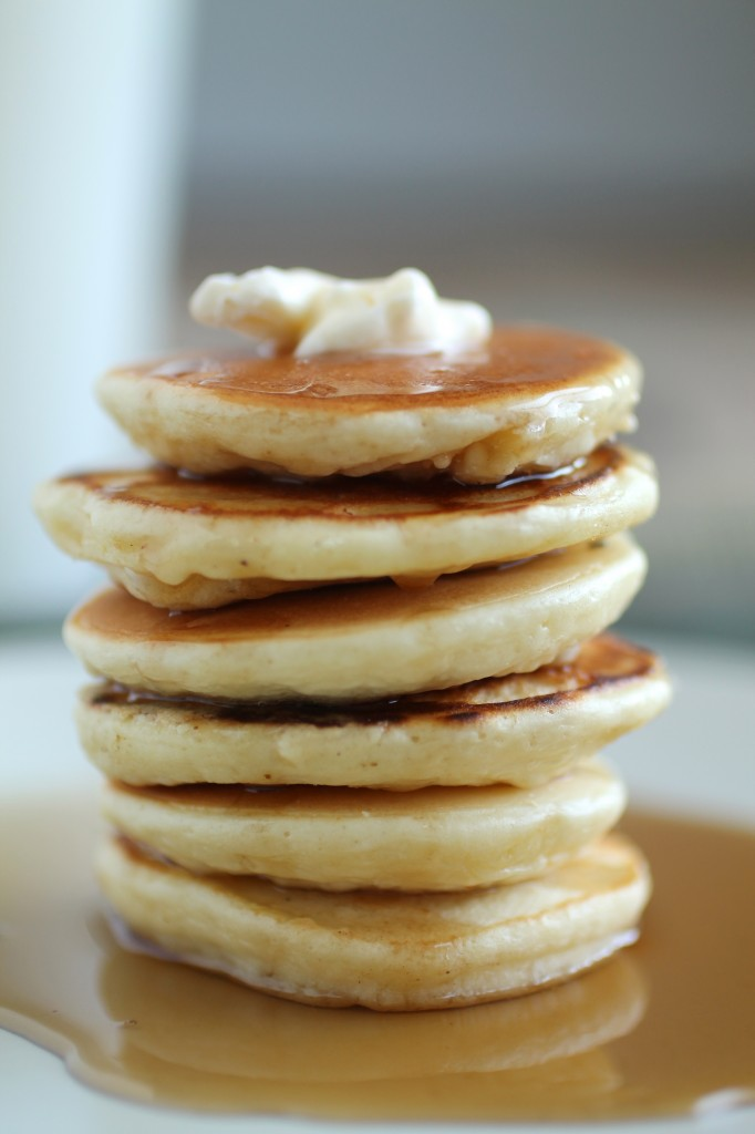 Stack of pancakes topped with a pat of butter, with maple syrup running down the sides.