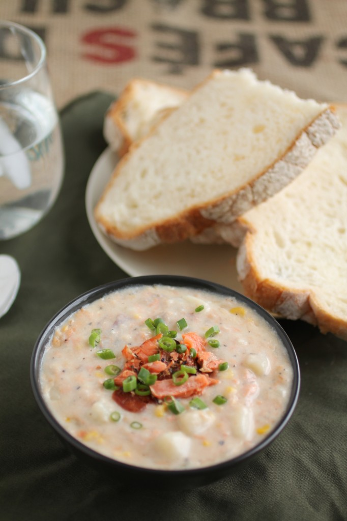 Chowder in a black bowl, topped with smoked salmon pieces and sliced green onions, next to a plate of fresh sliced bread.