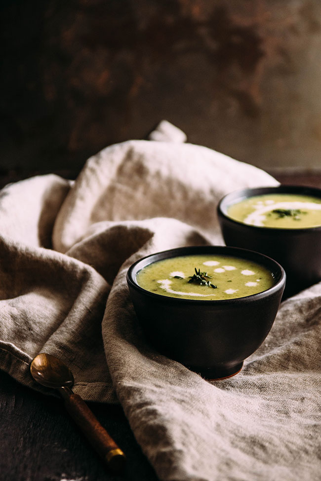 Side photo of green cream of leek and potato soup in a small black bowl atop a light brown linen napkin with a second bowl of soup in the background