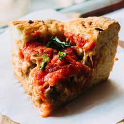 Slice of deep dish pizza topped with fresh basil.