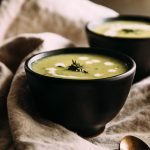 Soup in a black bowl, garnished with fresh thyme and drops of heavy cream.