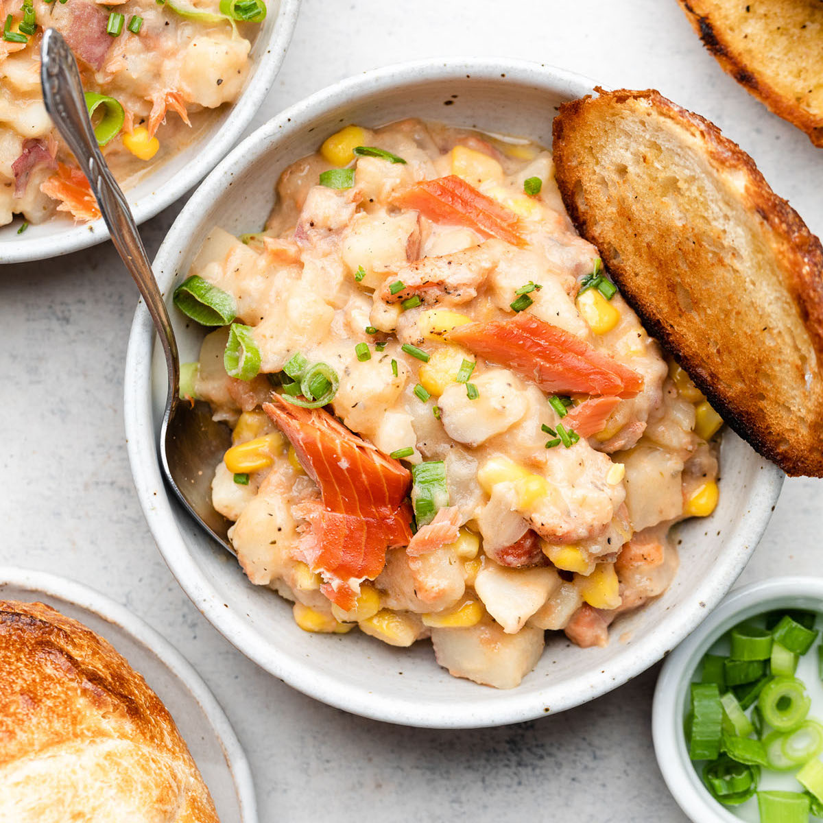 Salmon chowder in a white bowl with a piece of sourdough toast.