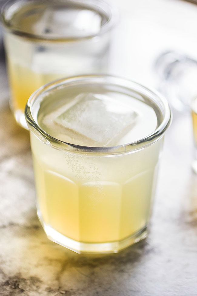 Whiskey lemonade in a short glass with a large square ice cube.