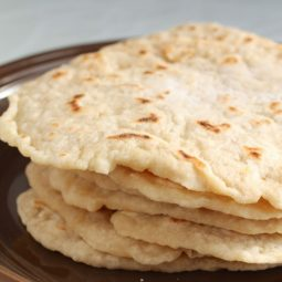 Stack of flour tortillas on a brown plate.