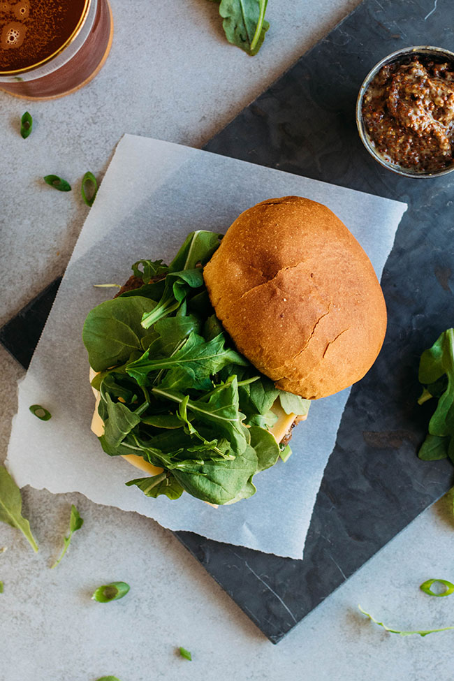 Overhead photo of cheeseburger with arugula and the top bun on the side, on a dark cutting board.