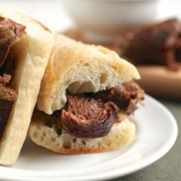 Two halves of a french dip sandwich stacked on a white plate with beef falling out.