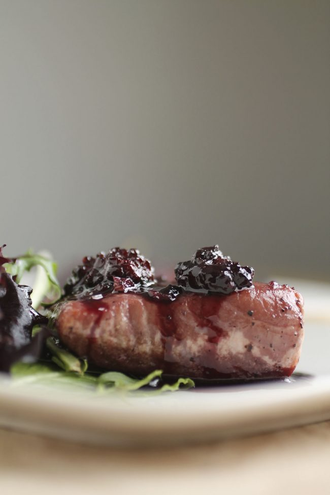 A piece of salmon topped with blackberry sauce next to a side salad.