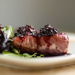 Salmon topped with blackberry sauce on a white plate.