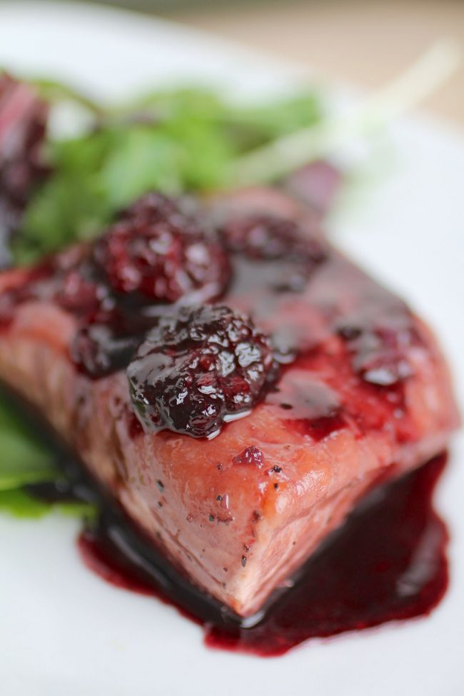 Close up of salmon with blackberry sauce drizzle on top.