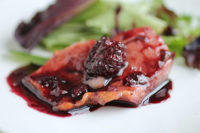 Salmon portion with blackberry sauce and a fresh blackberry on top.