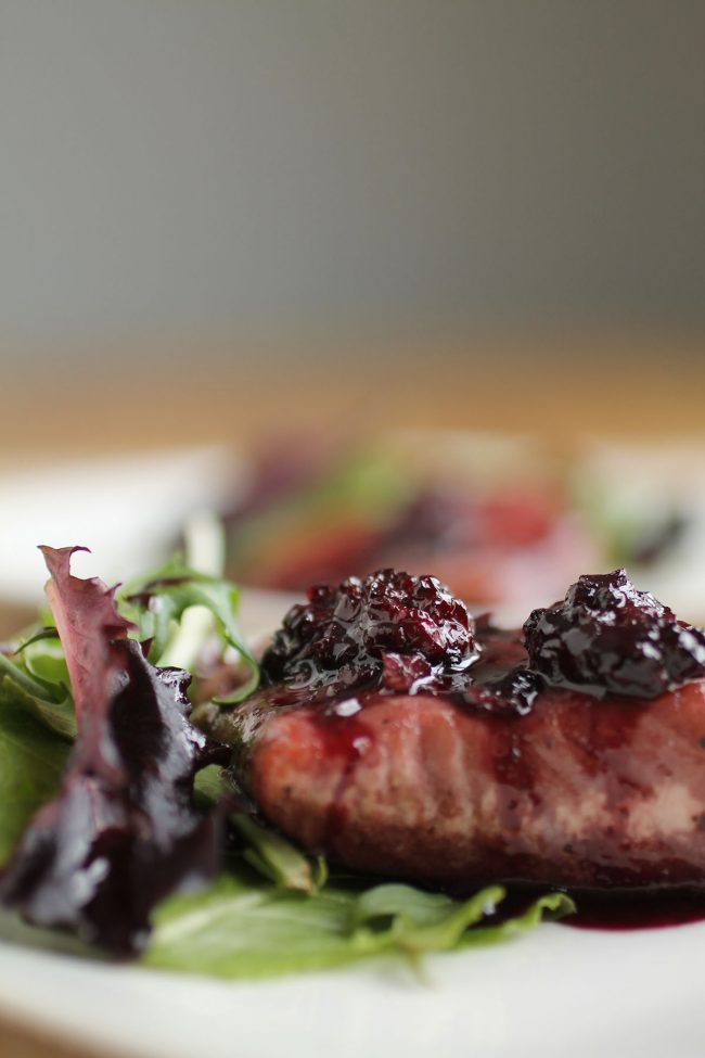Salmon topped with blackberry sauce next to mixed greens on a white plate.