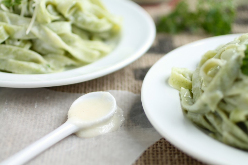 Spoonful of alfredo sauce laid next to a plate of spinach alfredo pasta.
