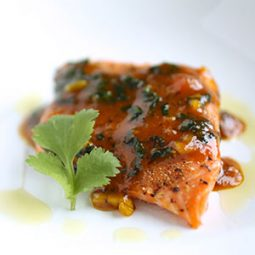 Salmon with orange sauce, topped with a sprig of fresh cilantro.